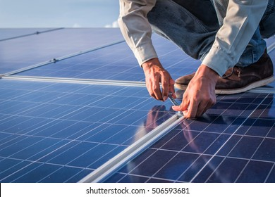 employee working on Wrench tightening solar mounting structure of photovoltaic panel at industry solar power