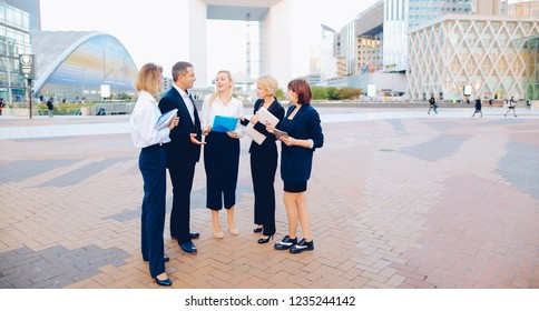 Employees of business of business organization working outside, talking by smartphone and discussing decisions. Concept of team work and biz solutions. Businesswoman shaking partner hand.