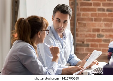 Employees business partners financiers working together analyzing financial report, businesswoman in glasses strategizing negotiating at meeting with middle aged businessman sitting at desk in office