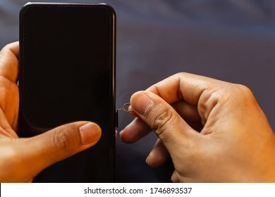 Employees are changing the phone SIM card, nano SIM card in the shop for customers to buy, Man's hand.