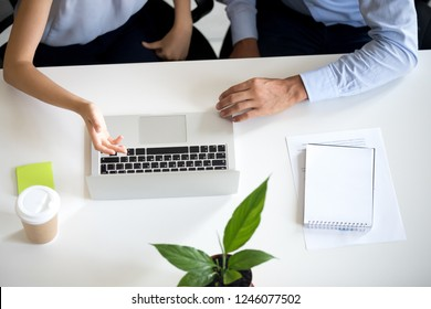 Employees colleagues using laptop together, discuss online project, mentor helping intern with pc software, explaining computer task, office workers brainstorming new idea, startup, hands top view