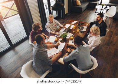 Employees of creative company are working on new startup and discussing idea of business development. Coworkers sit around wooden table and work on laptops and tablets. Concept of work in loft space