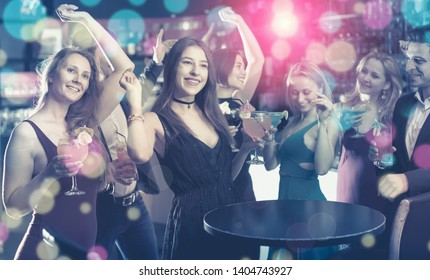 Employees dancing on corporate party with alcohol in hands