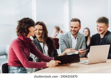 employees discuss working documents sitting at a Desk