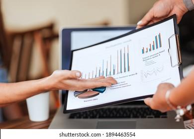 employees discussing financial data near the desktop.