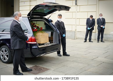 Employees of the funeral services company next to the coffin of a COVID-19 victim, in Turin, Italy, April 2020.