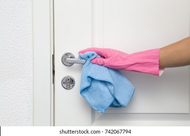 Employee's hand in rubber protective glove with rag wiping a door's handle. Maid or housewife cares about house. Spring general or regular clean up. Commercial cleaning company concept.