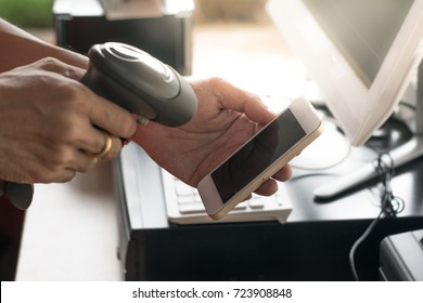Employees' hands are using barcode scanners to scan mobile screens.
