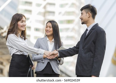 Employees having a business meeting on city background,Happy smiling business team in office,Business partners working, multi ethnic group of people, city,Business people working outside office