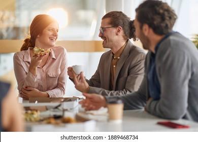 Los empleados se divierten en el almuerzo en la cafetería de la empresa en un ambiente alegre. Personas, trabajo, empresa, concepto de negocios.
