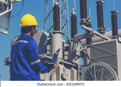 Employees are monitoring the operation of large transformers.