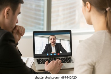 Employees participate virtual conference with boss running business remotely, businesspeople hold online meeting on laptop group chat, entrepreneurs making video call to partner, close up rear view