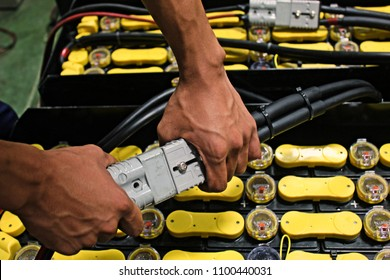 Employees are plugged in the battery for the electric forklift. To charge the battery ready for use.
