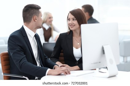 employees sitting behind a Desk in the office