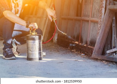 Employees at a termite control company are using a chemical sprayer to get rid of termites at customers' homes and search for termite nests to eradicate them. Chemical spray ideas to prevent insects.