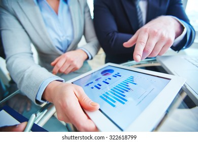 Employees with touchpad consulting about review of marketing