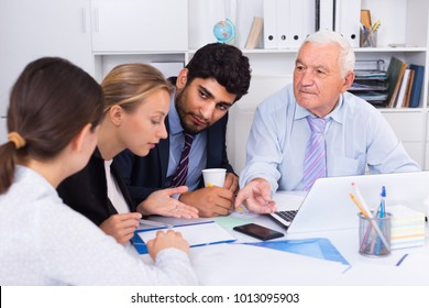 Employees are writing financial reports and discussing with mature boss in the office.