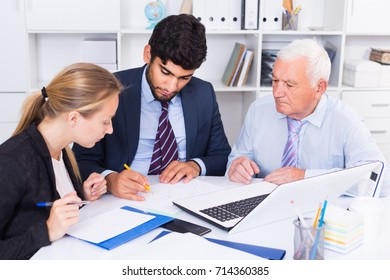 Employees are writing financial reports in the office.