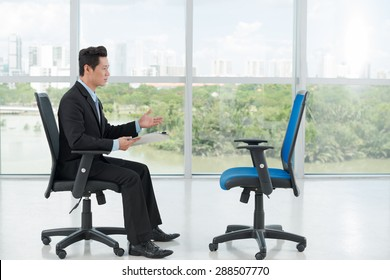 Employer interviewing an empty office chair, side view