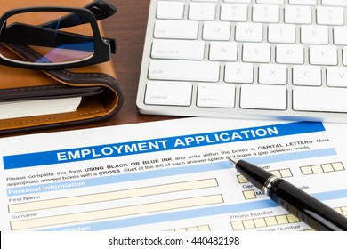 Employment application form with pen and keyboard; document is mock-up