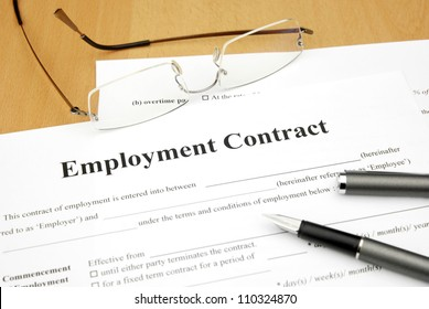 employment contract form with glasses and pen