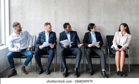 Employment Discrimination. Diverse Businessmen Staring At Lady Applicant Waiting For Job Interview Sitting On Chairs Indoor. Female Gender Prejudice At Work, Sexism And Career Inequality. Panorama