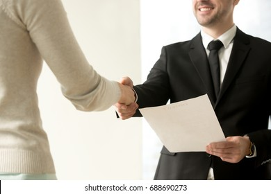 Employment handshake, smiling friendly employer shaking new hire hand, happy businessman holding document, giving official paper to businesswoman, offering job contract, focus on hands, close up view
