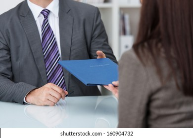 Employment interview with a close up view of a female applicant handing over a file containing her curriculum vitae to the businessman conducting the interview