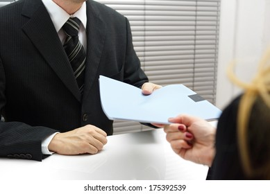 Employment interview with female applicant handing over a file containing her curriculum vitae to the businessman