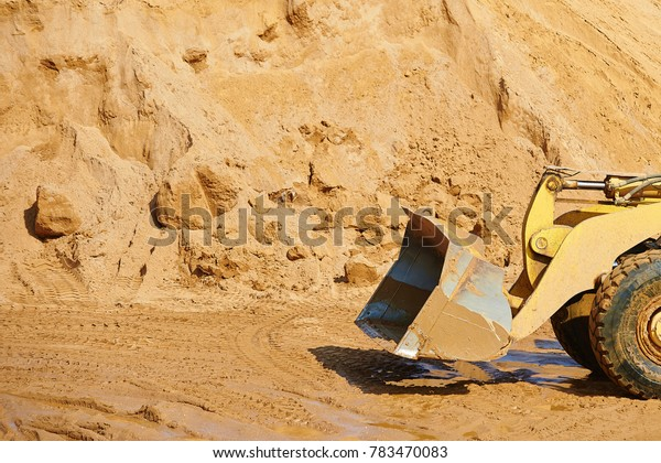 An emply scoop of an excavator or digger in a sand career
