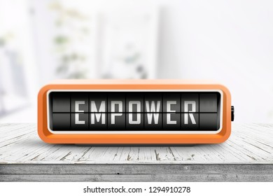 Empower message sign on a wooden desk with an orange retro device