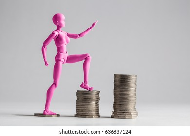 Empowered women stepping up the income ladder concept. Pink female figurine clilmbing up on piles of coins. Isolated on white with copy space.
