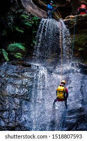 Empress Falls, Blue Mountains, Australia - Sept 7 2019: Man rappels down long drop cascading waterfall over slippery rocks, wearing backpack, with rope, wetsuit, helmet and climbing gear.