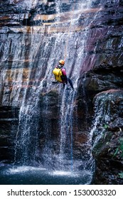 Empress Falls, Blue Mountains, Australia - Sept 7 2019: Man descending down cascading waterfall into deep pool, wearing backpack, with rope, wetsuit, helmet and climbing gear.