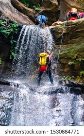 Empress Falls, Blue Mountains, Australia - Sept 7 2019: Man starts down long drop cascading waterfall over slippery rocks, wearing backpack, with rope, wetsuit, helmet and climbing gear.