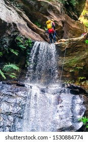 Empress Falls, Blue Mountains, Australia - Sept 7 2019: Guide get climber ready at the top of long drop cascading waterfall over slippery rocks, with rope, wetsuit, helmet and climbing gear.