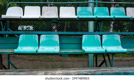 Empty 2 rows of simple  green, white plastic chairs attached to wooden bleachers to watch sport game. One is missing.