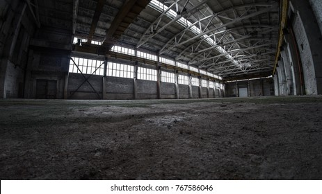 Empty abandoned plant. Floor is covered by green rod. Main constructions are made of concrete. It has crane beam ways. On top of columns are concrete truss structure. Factory has wide windows.