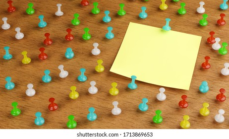 An empty adhesive note on a wooden bulletinboard surrounded by differently colored thumbtacks / pins.