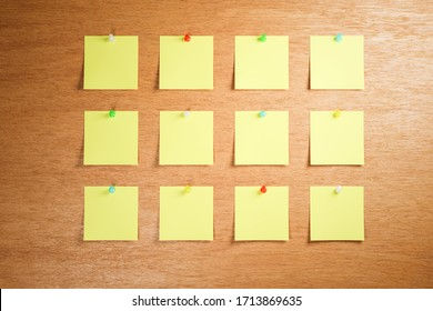 Empty adhesive notes attached to a wooden bulletin board. 3 rows with 4 pieces each. Differently colored thumbtacks / pins used.