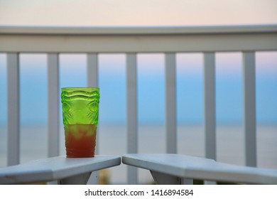 Empty Adirondack chairs look over the beach and ocean at sunset.  A beverage is ready for this relaxing lifestyle vacation image.