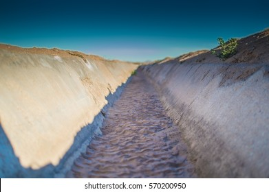 An empty agricultural irrigation canal with dirt in it