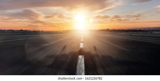 Empty airplane runway with dramatic sunset light. Travel and transportation concept.