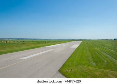 Empty airport runway with green grass and blue sky in the horizon.