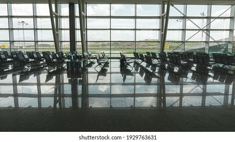 Empty airport seats in front of windows background. Modern waiting hall in city airpot for business or other travels. Reflection of sky and modern metal seats in airport waiting platform.