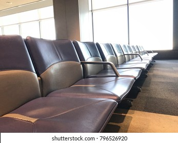 Empty airport terminal waiting area with gray and violet seats