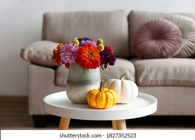 Empty apartment with minimalistic style interior, coffee table with autumnal bouquet in a vase and mini pumpkins on foreground. Copy space for text, background, close up.