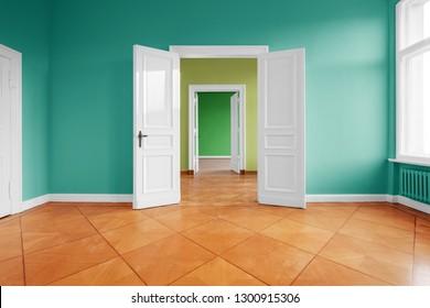 empty apartment room with wooden floor and open wing doors