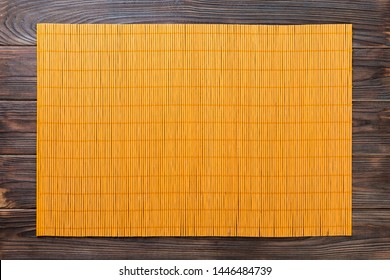 Empty Asian Food Background. Yellow Bamboo mat on wooden background top view with copy space flat lay.