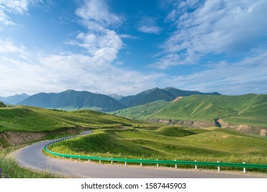 Empty asphalt curvy rural road winding on alpine meadows in mountain ranges with blue sky in the Tien Shan mountains in Xinjiang of China